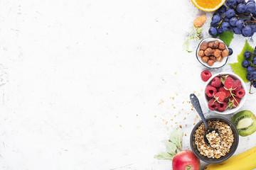 Ingredients for healthy breakfast meals: raspberries, blueberries, nuts, orange, bananas, grapes blue, green, apples, kiwi. Top View.