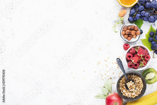 Ingredients for healthy breakfast meals: raspberries, blueberries, nuts, orange, bananas, grapes blue, green, apples, kiwi. Top View.