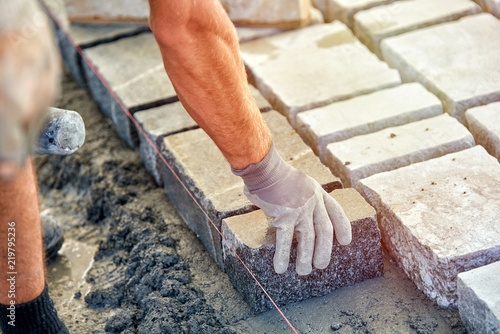 Fotografía  A workman's gloved hands use a hammer to place stone pavers