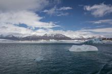 Icebergs In Jökulsárlón Glacier Lagoon On Iceland Overseeing A Mountain