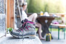 Paar Bergschuhe Auf Alm, Hölzerne Veranda, Tisch Mit Wanderer Im Hintergrund