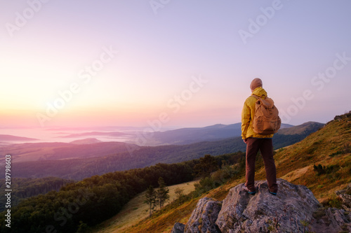 Fotografie, Obraz Alone tourist on the edge of the cliff against the backdrop of an incredible mountain landscape