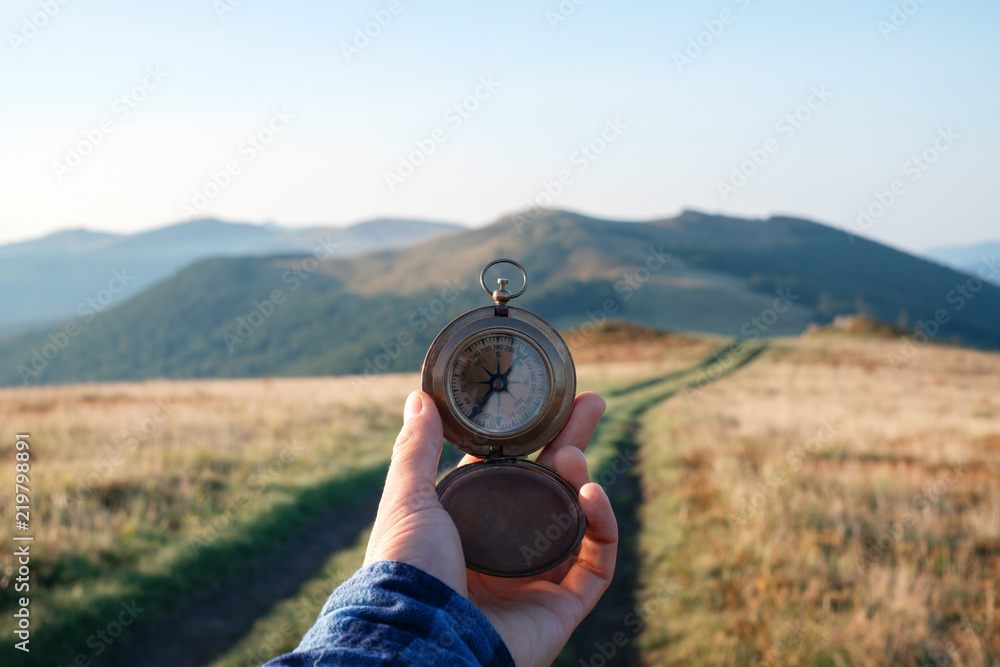 Fototapeta Man with compass in hand on mountains road. Travel concept. Landscape photography