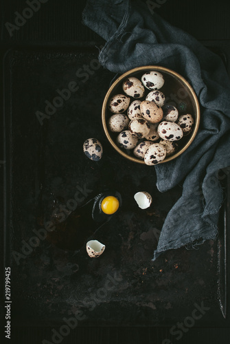 Fresh organic quail eggs in a metal vintage sieve on an old grunge dark background. Dark and moody picture. Low key. Toned image. Top view. Copy space