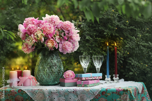 A bouquet of romantic pink peonies in a glass vase. Dinner by candlelight in the garden.