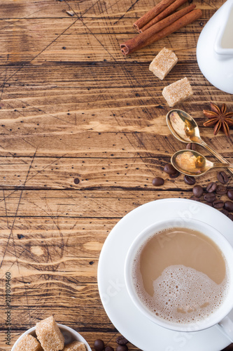 Foto op Canvas Cafe Cup of coffee, brown sugar and cinnamon with anise on a wooden background. Copy space