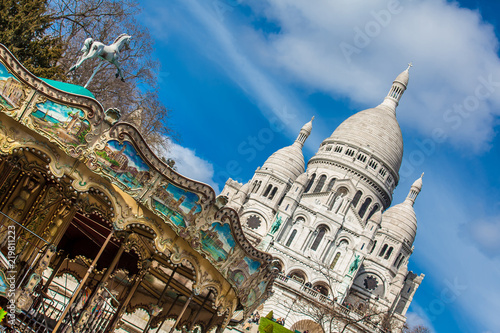 фотография PARIS, FRANCE - MARCH, 2018: Carrousel and the Sacre Coeur Basilica at the Montm