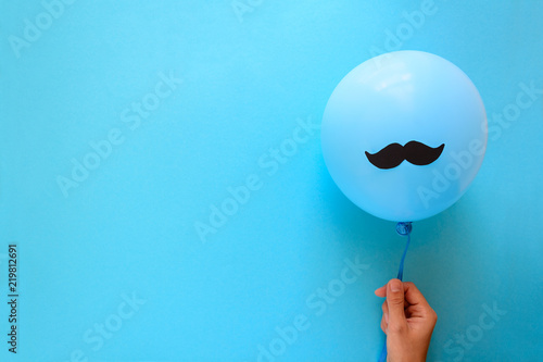 Photo  Hand holding blue balloon with a paper mustache on blue paper background