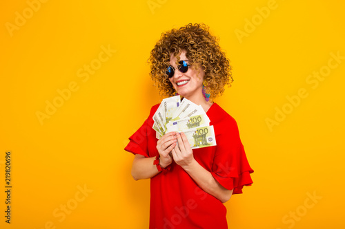 Fotografía  Attractive woman with short curly hair with cash