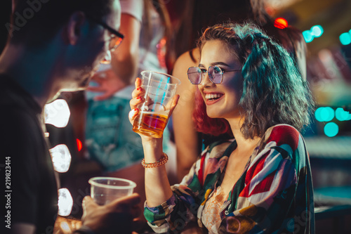 Canvas Print Young woman at the festival drinking beer with boyfriend