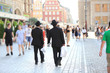 Dwóch mężczyzn w czarnych kapeluszach i garniturach idą z reklamówkami przez miasto.