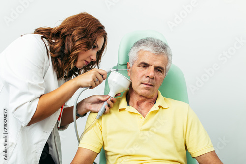 Senior man at medical examination or checkup in otolaryngologist's office Canvas-taulu
