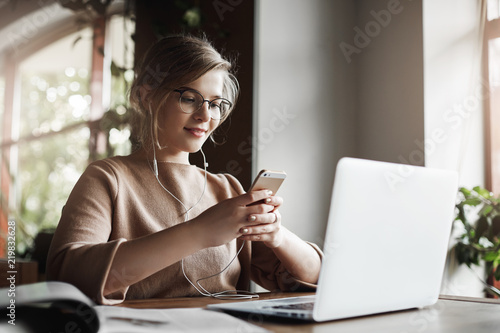 Woman studying and preparing project via laptop, wearing earphones, listening music joyfully, holding smartphone and reading answear on message, being intrigued with future date, taking break - 219832628