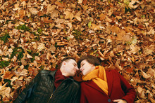 Top View Portrait Of Young Romantic Couple In Love Woman And Man With Closed Eyes Facing Each Other Lying On Fallen Leaves In Autumn City Park Outdoors. Love Relationship Family Lifestyle Concept.