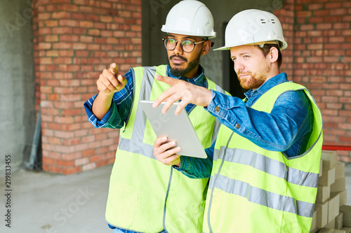 Fotografia Waist up portrait of two civil engineers wearing hardhats discussing constructio
