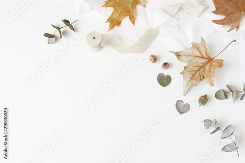 Fall creative styled composition. Autumn floral arrangement with dry eucalyptus, maple leaves and silk ribbon on white table background. Feminine flat lay, top view. Empty space.