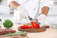 Professional Chef Cutting Pepper On Table In Kitchen, Closeup