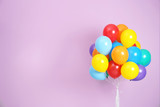 Fototapeta Tęcza - Bunch of bright balloons and space for text against color background