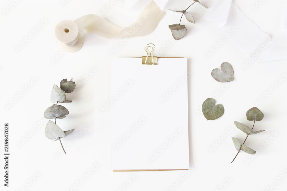 Fototapety, obrazy: Feminine wedding desktop stationery mockup with blank greeting card, dry eucalyptus leaves, silk ribbon and golden binder clip on white table background. Flat lay, top view. Styled stock photo.