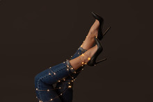 Legs Of A Woman In Jeans And Shoes Decorated With Yellow Garlands Around A Black Background