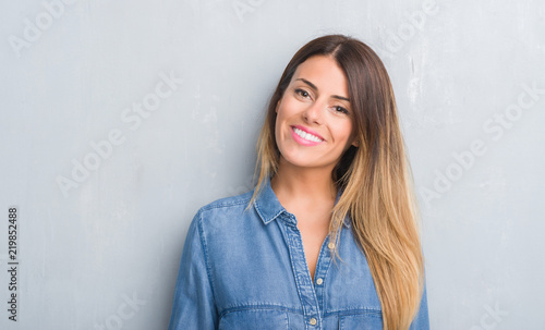 Obraz na plátně Young adult woman over grey grunge wall wearing denim outfit with a happy face s