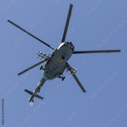 Poster Helicopter Military helicopter maneuvers in the blue sky