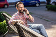 Cheerful adult man talking on phone outdoors