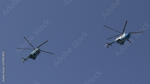 Tuinposter Helicopter Several military helicopters fly side by side against the blue sky