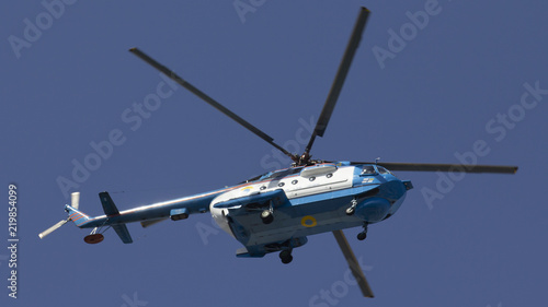 Tuinposter Helicopter Military helicopter maneuvers in the blue sky