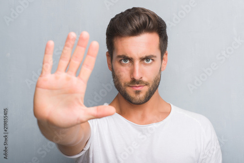 Obraz Handsome young man over grey grunge wall with open hand doing stop sign with serious and confident expression, defense gesture - fototapety do salonu