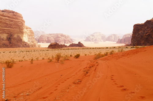 Foto op Canvas Baksteen Wadi Rum desert, Jordan, Middle East, known as The Valley of the Moon. Orange sand, blue sky, haze and clouds. Designation as a UNESCO World Heritage Site. Red planet Mars landscape.