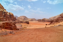 Wadi Rum Desert, Jordan, Middle East, The Valley Of The Moon. Orange Sand, Haze, Clouds. Designation As A UNESCO World Heritage Site. Red Planet Mars  Landscape. Offroad Adventures Travel Background.
