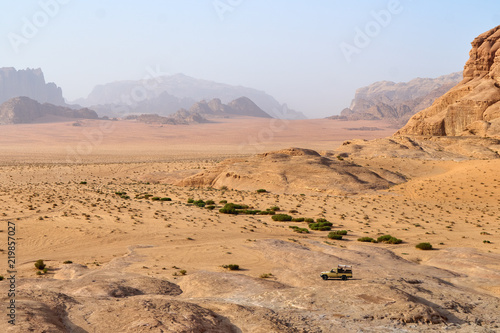 Safari jeep car in Wadi Rum desert, Jordan, Middle East, known as The Valley of the Moon. Sands, blue sky clouds. Designation as a UNESCO World Heritage Site.