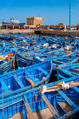 Stickers pour portes Maroc A fleet of blue fishing boats huddled together in the port of Essaouira in Morocco. You can also see the fortifications and a tower of the citadel of Mogador