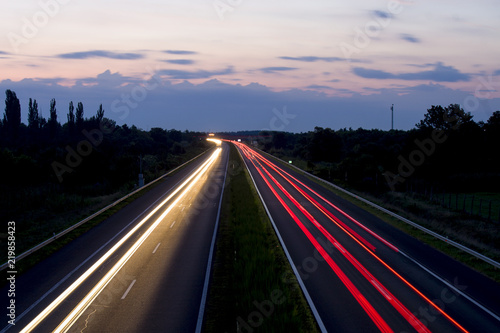 Hungarian highway at night showing vehicles lights, low shutter speed, top view, sky background.
