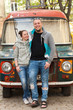 Closeup of family couple near colorful paintyng old car or gypsy hippie van. Happy romantic young couple in love enjoying in moments of happiness. Love, dating, romance.