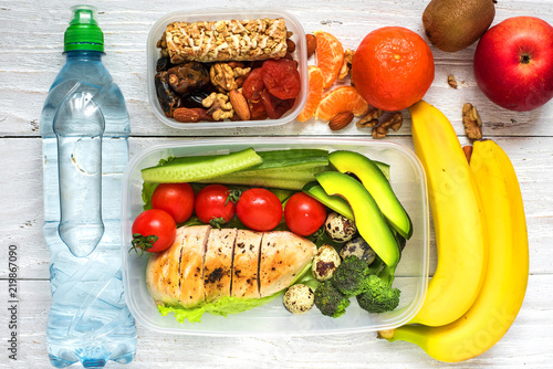 Healthy lunch boxes with chicken, fresh vegetables, fruits and nuts with bottle of water on white wooden background