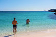 Tourists Snorkeling In The Azure Blue Water Of A White Silica Sand Beach In Whitsundays Australia