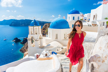 Europe Summer Vacation Tourist Woman Walking In Oia City At Three Blue Domes Church, Santorini, Greece. Famous Cruise Travel Destination, Mediterranean Sea.