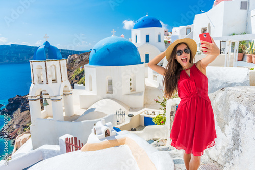 Fototapeta Santorini tourist girl on cruise holiday taking selfie photo with phone at famous three domes church, European tourism attraction in Greece. Asian woman on vacation. obraz