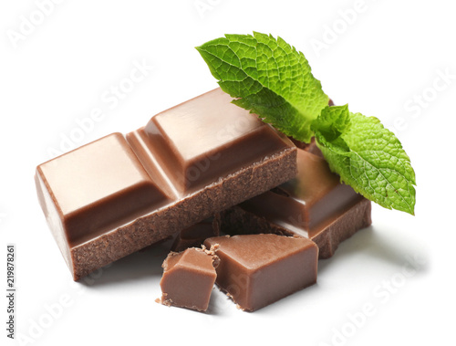 Pieces of milk chocolate with mint on white background