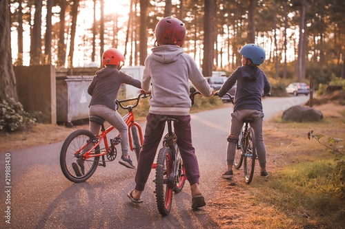 a group of boys on their bikes in the summer during sunset in a campground