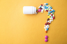 Pills Or Capsules As A Question Mark And White Plastic Bottle.