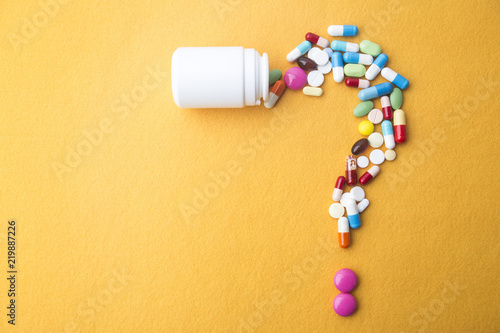 Fotografia Pills or capsules as a question mark and white plastic bottle.