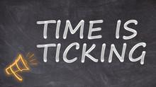 Time Is Ticking Written On Blackboard With Megaphone