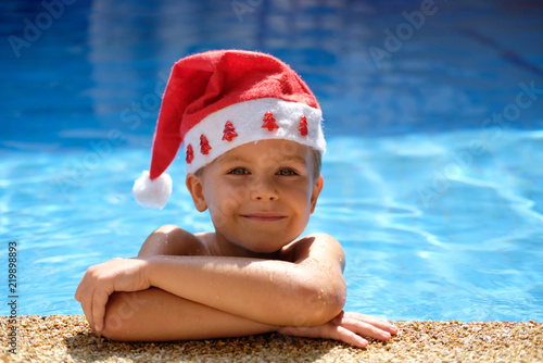 Boy in pool with santa hat. Concept: christmas holiday in hot country