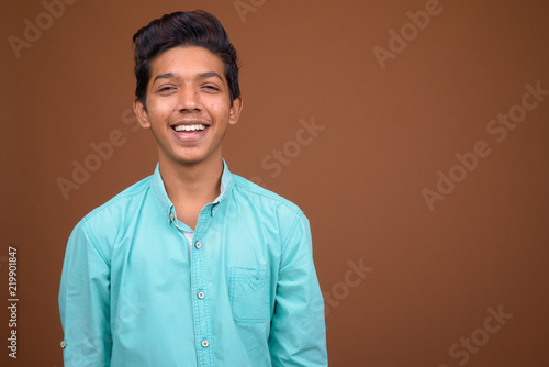 Fotografiet  Young Indian boy wearing blue shirt looking smart against brown
