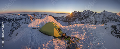 Poster Nouvelle Zélande Yellow tent pitched up on a summit of a high alpine peak. Winter camping in snow covered alpine like mountains. Winter alpine landscape, climbing bivouac panorama. Vibrant blue sky, sunset or sunrise.