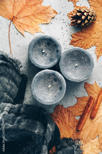 Obraz Top view of autumn still life on a grey concrete background. Maple leaves, black aromatic candles and warm scarf. - fototapety do salonu