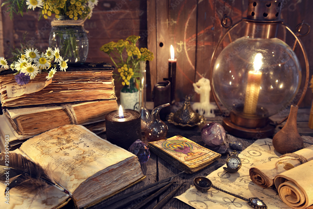 Fototapeta Still life with old-fashioned lamp, magic witch books, tarot cards and old papers. Mystic background with ritual esoteric objects, occult, fortune telling and halloween concept